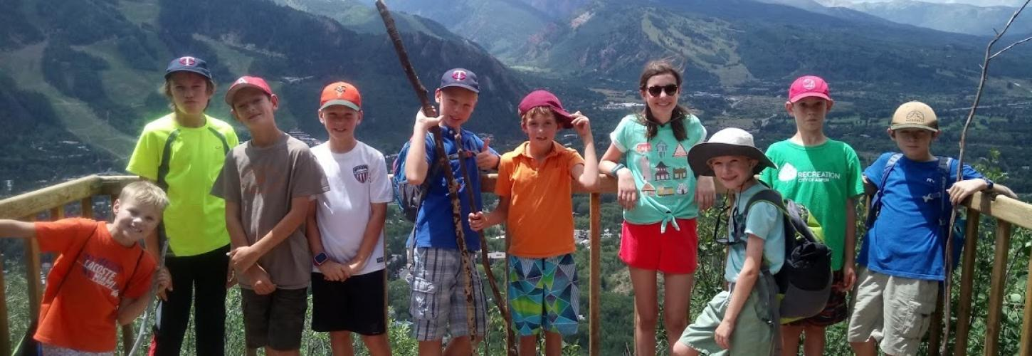 Kids posing on viewing platform with mountains behind them.