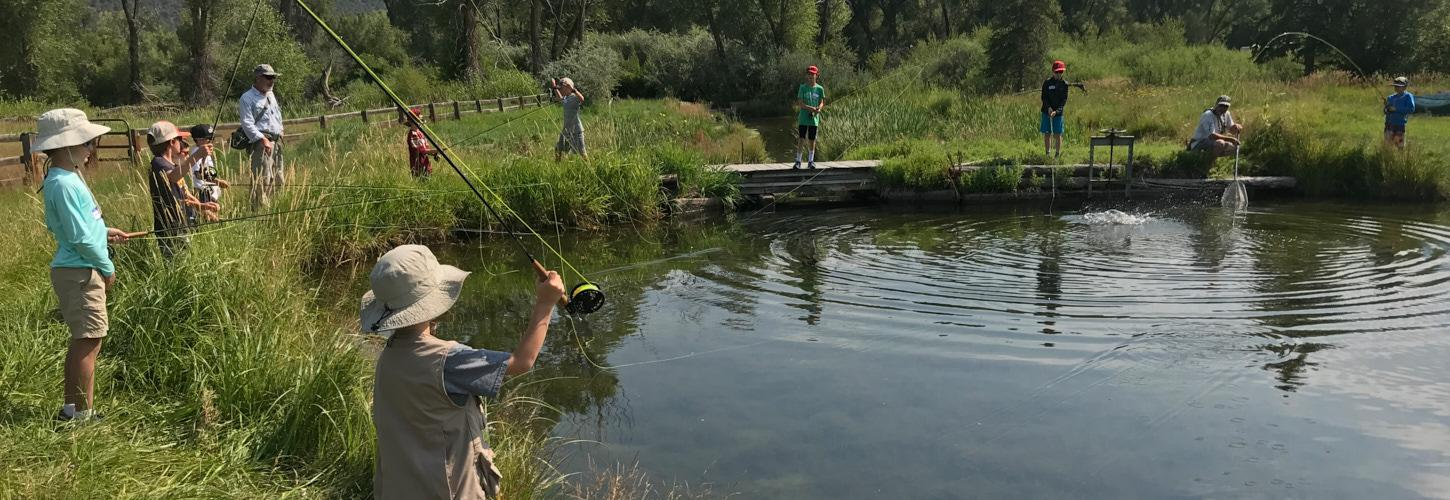 Kid standing at the edge of a pond fishing