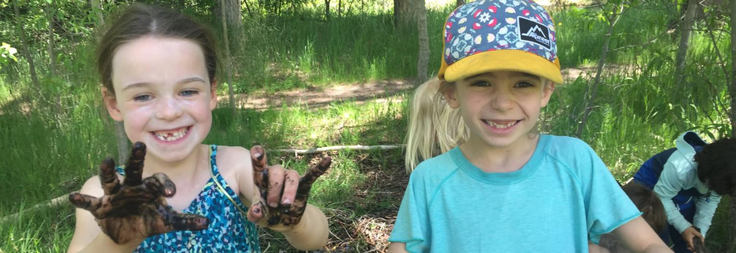 Smiling summer camp kids with muddy hands