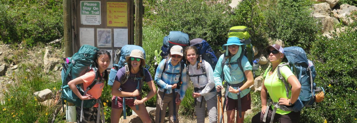 Girls standing at trailhead with backpacks on a smiling faces
