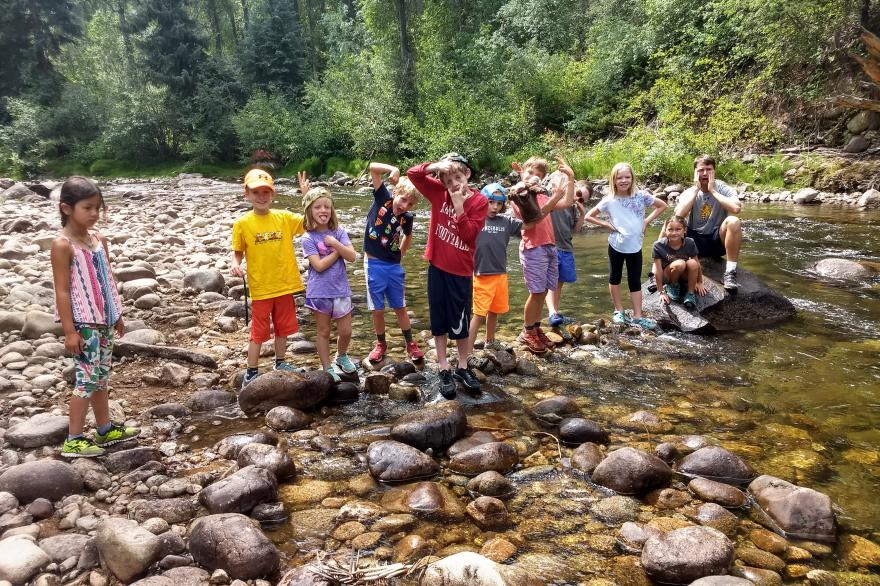 Kids standing in a stream bed looking for macro-invertebrates