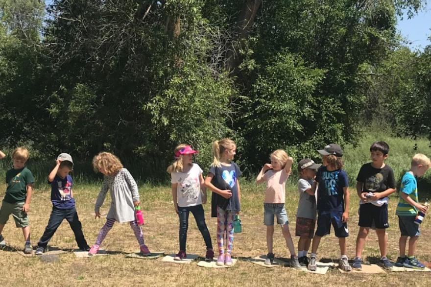 Kids playing a line game in a field
