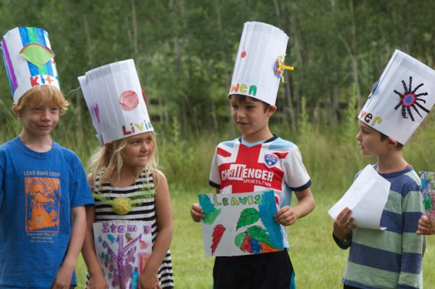 Kids standing in a line with decorated chef hats on