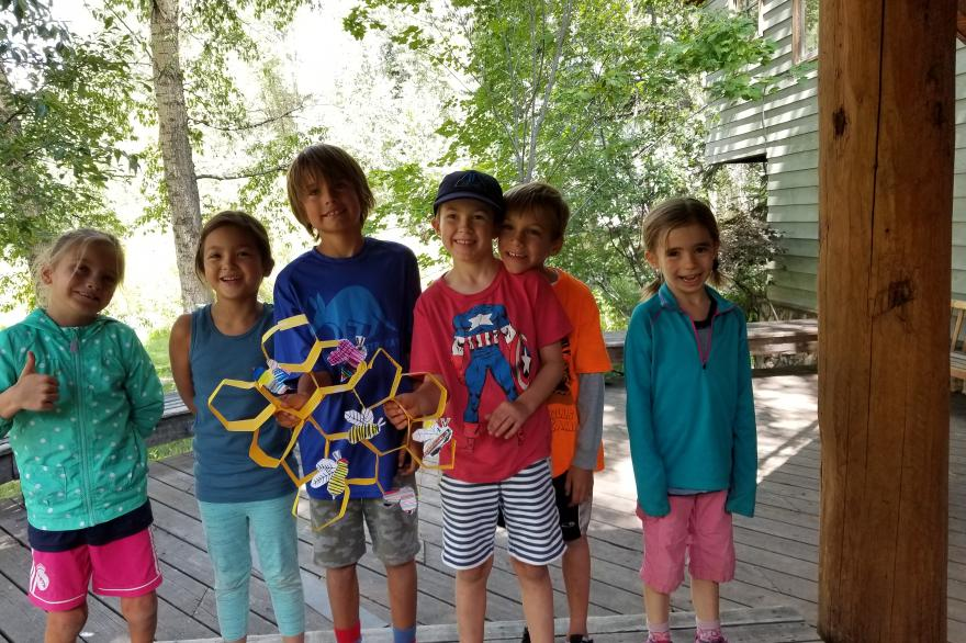 Kids holding a visual representation of the hexagons in a beehive.