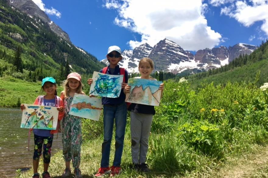 Kids with paintings standing with the maroon Bells mountains in the background